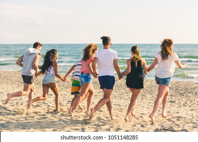 Multiracial group of friends running on the beach. There are four girls and three boys, wearing trunks and colourful t-shirts. Friendship and lifestyle concepts.