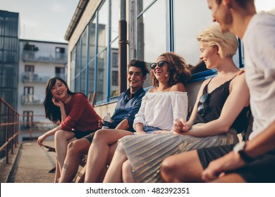 Multiracial group of friends sitting in balcony and smiling. Young people relaxing outdoors in terrace.