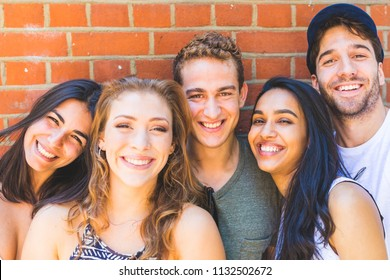 Multiracial group of friends taking a selfie together. Photo of young best friends smiling at the camera while taking a photo. Lifestyle and friendship concepts