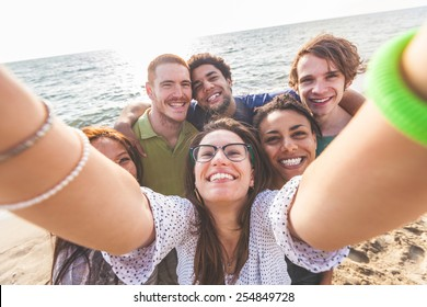 Multiracial group of friends taking selfie at beach. One girl is asiatic, two persons are black and three are caucasian. Friendship, immigration, integration and summer concepts.