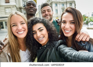 Multiracial group of friends taking selfie in a urban street with a muslim woman in foreground. Three young women and two men wearing casual clothes.