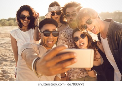 Multiracial group of friends taking selfie on a beach