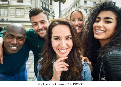 Multiracial group of friends taking selfie in a urban street with a caucasian brunette woman in foreground. Three young women and two men wearing casual clothes.