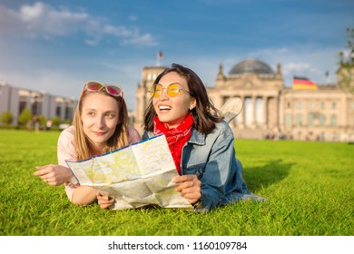 Multiracial group of friends visiting the city of Berlin. Two women reading map with Reichstag building on the background. Friendship and travel concept with real candid emotions