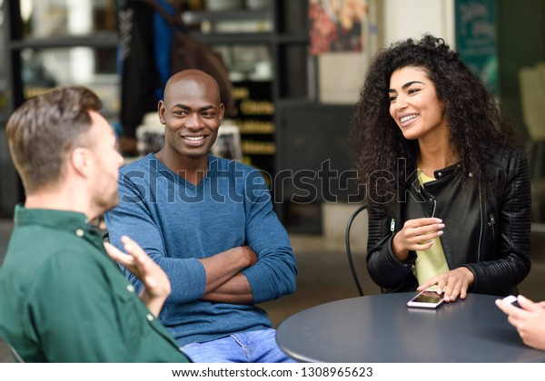 Multiracial group of friends waiting for a coffee together. Two men and a man sitting at cafe, talking and smiling. Lifestyle and friendship concepts with real people models