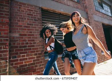 Multiracial group of friends walking down the city street. Three young women walking outdoors on road.