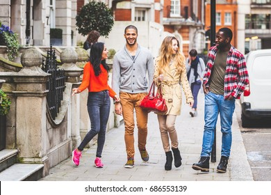 Multiracial group of friends walking in London. Two couples, talking and laughing. Residential district with houses and cars on background. Lifestyle and friendship concepts.