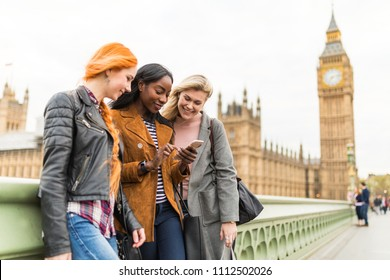 Multiracial group of girls in London looking at mobile phone with Big Ben on background. Three women in London having fun together. Travel and friendship concepts