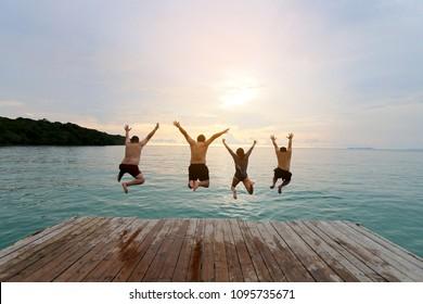 Multirassische Gruppe glücklicher junger Menschen, Familie, Freunde, die von der Holzbrücke zum Meer springen, mit schönem blauen Himmel im Sommer nahe dem Strand.Glück, Erfolg, Freundschaft und Gemeinschaftskonzept