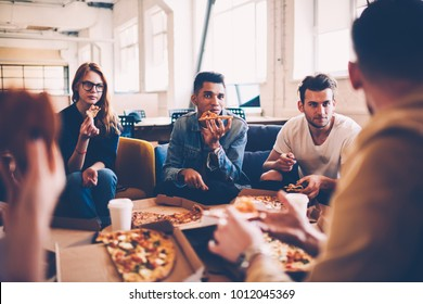 Multiracial group of international student talking to each other and making friends during pizza party, hungry male and female employees having lunch break together eating in coworking space