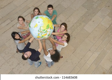 Multiracial group of people holding  the Earth Globe showing Europe