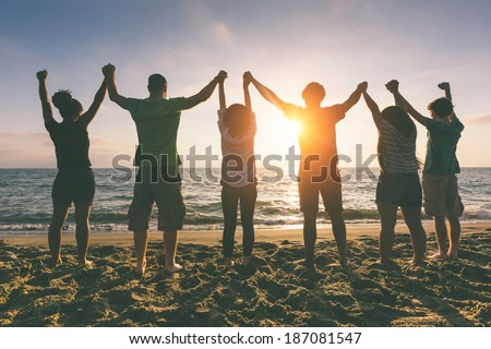 Multiracial Group of People with Raised Arms looking at Sunset