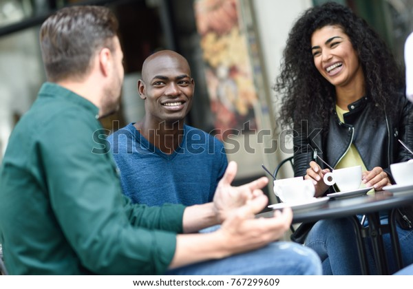 Multiracial group of three friends having a coffee together. A woman and two men at cafe, talking, laughing and enjoying their time. Lifestyle and friendship concepts with real people models