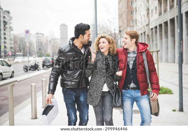 Multiracial group of two men and woman friends outdoor in town happy walking hugging through the streets - teamwork, friendship, relax concept