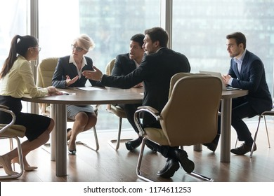 Multiracial group of workers disputing quarreling in office at meeting. Unsatisfied colleague boss explaining arguing criticize the work of young asian girl intern. Problems mistakes in work concept