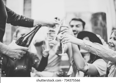 Multiracial group of young friends having fun drinking and toasting glasses of champagne on university stairs - Happy people celebrating graduation with a bottle of prosecco in city outdoor