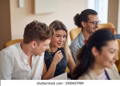 multiracial group of young people having fun at business seminar, talking, smiling