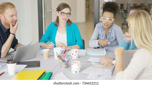 Multiracial group of young workers communicating in process of discussing graphics and statistics at table.
