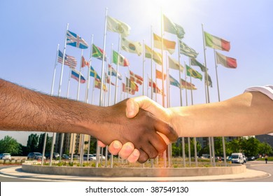 Multiracial handshake with world flags background - Black and white men hand shake team against racism - Governance leaders agree solution to actual refugees political events concept - Focus dark hand