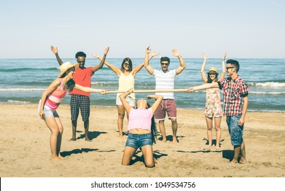 Multiracial happy friends group having fun together with limbo game at beach - Summer joy and friendship concept with young multi ethnic people playing on spring break vacation - Warm bright filter