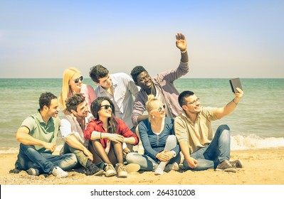 Multiracial happy friends taking selfie with tablet at beach - Multi ethnic concept of happiness and modern friendship all together against racism for peace and fun - Saturated vintage filtered look