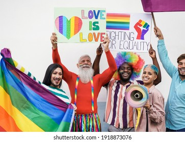 Multiracial homosexual people having fun at lgbt pride parade outdoor with banner and rainbow flag