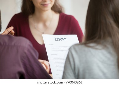 Multiracial hr holding resume at job interview with woman candidate, recruitment team read applicant cv at hiring negotiations concept, human resources recruiters with curriculum vitae, close up view