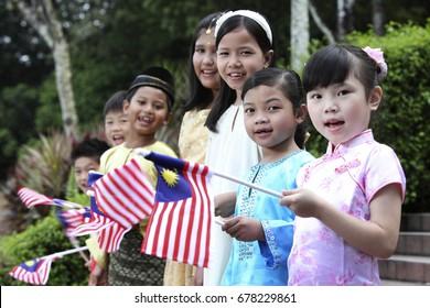 Multiracial kids holding Malaysia flag and looking at camera