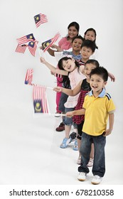 Multiracial kids line up in a row, holding Malaysia flags