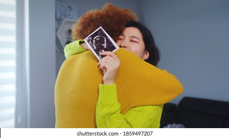 Multiracial lesbian couple expecting baby. Embracing with ultrasound baby picture. Maternity support. High quality photo