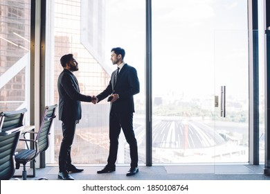 Multiracial male employees in formal clothing doing handshake during business meeting in office enterprise for find solutions negotiations, proud ceo found merger agreement of acquisition on deal