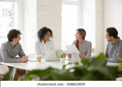 Multiracial male and female colleagues discussing document at team meeting or corporate office briefing, diverse friedly african and caucasian partners talking about contract at group negotiations