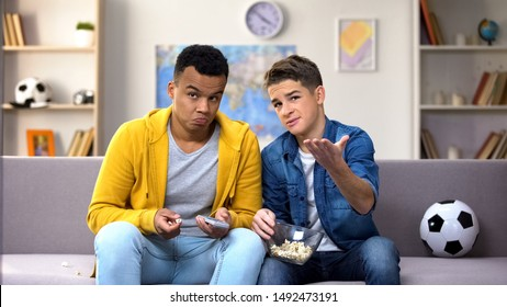 Multiracial male teen friends discussing football match eating popcorn, leisure