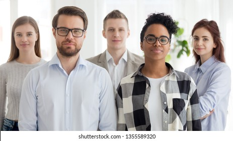 Multiracial man and woman leaders with team looking at camera. Portrait of serious businessman, black businesswoman with office workers on background. Team work, happy personnel, staff, management