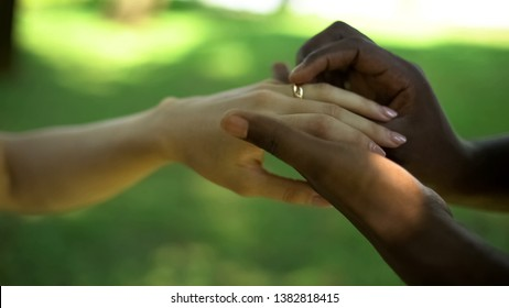 Multiracial marriage, male hand puts golden ring on brides finger, wedding time