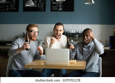 Multiracial men drinking beer celebrating victory watching online football game match on laptop in pub restaurant, diverse friends supporting team excited with goal result, sport betting win concept