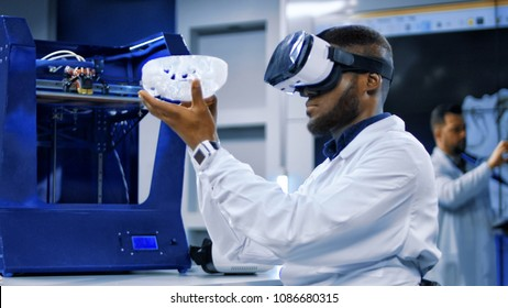 Multiracial men in medical gown exploring 3d scull model in VR glasses.