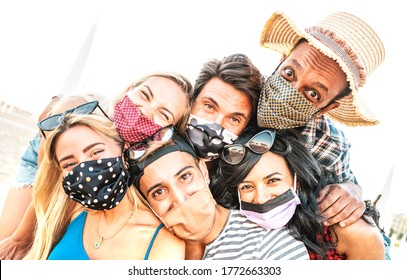 Multiracial milenial friends taking selfie smiling behind face masks - New normal summer friendship concept with young people having fun together - Warm bright backlight filter with tilted composition