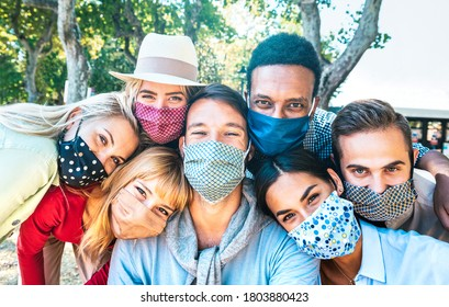 Multiracial milenial friends taking selfie with closed face masks during Covid second wave outbreak - New normal lifestyle concept with young people having fun together - Bright vivid backlight filter