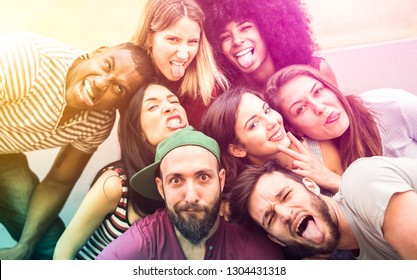 Multiracial millenial friends taking selfie with funny faces - Happy youth friendship concept against racism with international young trendy people having fun together - Psychedelic radial filter