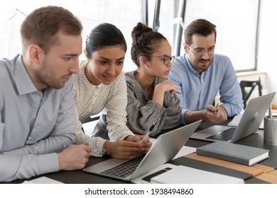 Multiracial millennial employees involved in project development, working in small groups on laptops, sitting together at desk in office, diverse teammates brainstorming using computer applications.