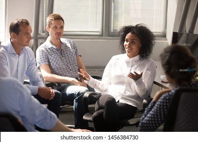 Multiracial millennial employees sit in circle involved in teambuilding office activity, talk and shared thoughts, diverse colleagues brainstorm speaking during group meeting or informal briefing