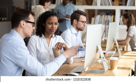 Multiracial millennial people sitting in modern coworking office, mentor teach trainee new employee pointing looking at computer screen explain corporate program. Help assistance and mentoring concept