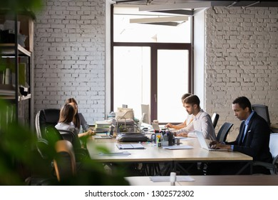 Multiracial office employees sit at coworking table, busy with laptops, diverse workers or colleagues collaborating in shared workplace, working at computers, discussing business issues