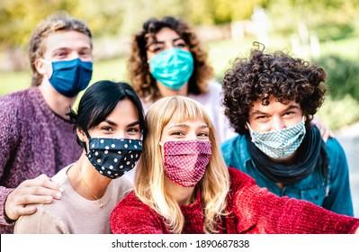 Multirassische Menschen, die sich mit Gesichtsmaske und Federkleidung selbst tragen - Neues normales Lifestyle-Konzept mit jungen Freunden, die sich draußen amüsieren - Heller Filter mit Fokus auf mittleres blondes Mädchen