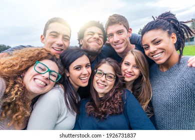 Multiracial people together in a selfie making funny faces - Group of friends with mixed races having fun together at park - Friendship and lifestyle concepts