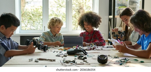 Multiracial school kids students making robotic cars using tablet computer. Diverse junior children pupils building robot vehicle learning at table at STEM code ai engineering science education class.