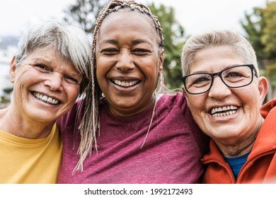 Multiracial senior women having fun together after sport workout outdoor - Main focus on african female face
