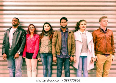 Multiracial serious people lineup as mugshot is standing next to metal rolling shutter - Unemployed multi ethnic friends line up outdoor - Concept of discrimination and youth concern for the future