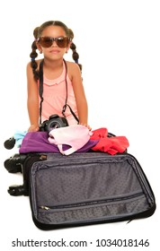 Multiracial small girl with sunglasses and a camera opening a travel suitcase - Isolated on a white background